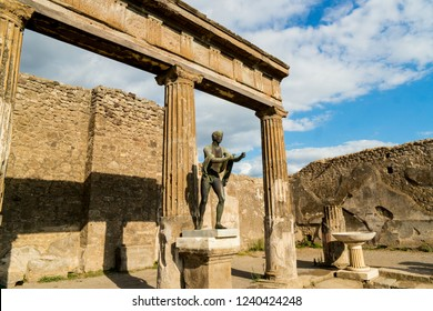 The View of the Ruins of the antique Temple of Apollo with bronze Apollo statue in Pompeii, Naples, Italy.