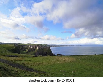 View of the Ruins of Dunluce Castle, a medieval Irish castle in a cliff by the sea.