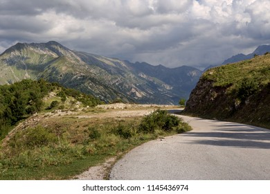 View of a rural road and mountains in a summery, cloudy evening (region Tzoumerka, Greece, mountains Pindos).