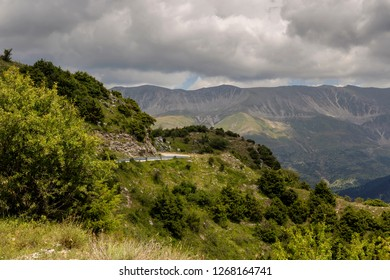 View of a rural road and mountains in a summery, cloudy day (region Tzoumerka, Greece, mountains Pindos).