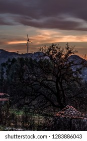 View of a rural scenario on sunset, wind turbine on top of mountains and dramatic sunset sky as background, in Portugal.