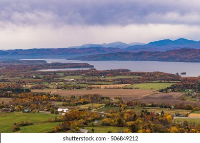 view of rural Vermont farm valley in autumn  with Lake Champlain and the Adirondack Mountains  in distance