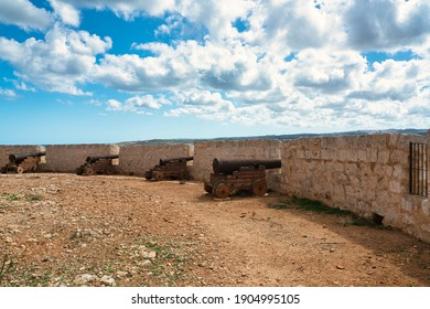 View of the rusted cannons at Saint Mary's Battery. A historic artillery battery from the 18th century on the island of Comino in malta. A popular tourist destination on the coastline on a sunny day.