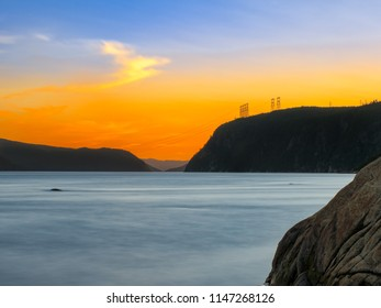 View of the Saguenay Canadian Fjord at sunset, orange sky and surface fog on the water