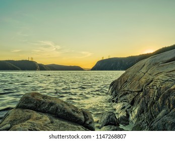 View of the Saguenay Canadian Fjord at sunset, large boulders detailed in the foreground