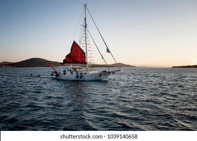 View of a sailboat, Aegean sea and landscape in Cunda (Alibey) island at sunset.