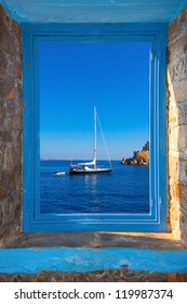 View of a sailing boat threw a window  in Santorini island Greece