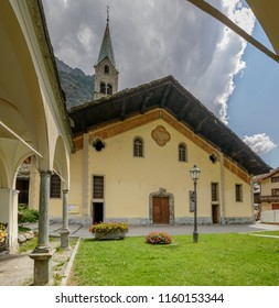 view of saint Giovanni Battista church facade on churchyard, shot on a bright summer day at Gressoney Saint Jean,  Lys valley, Aosta, Italy