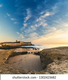 View of Saint Julian Fortress with lighthouse tower from beach (praia) of Carcavelos, Portugal. Ocean waves from the Atlantic, and eroded beach rocks.