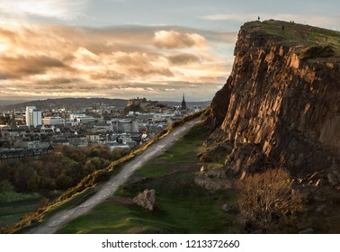 View of the Salisbury Crags at Holyrood Park, in Edinburgh, Scotland, with Edinburgh's Castle in the background, and evening light on the face of the cliffs and the clouds. Landscape. Cityscape. Trave