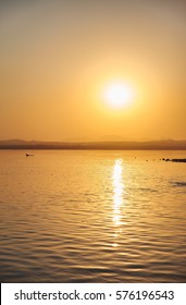View of the salt lake with a beautiful pink water. Sunset orange sun, the neighborhood.Las salinas, Torrevieja, Spain