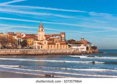 View of San Lorenzo ocean beach and San Pedro church in Gijon, Asturias, the Northern Spain