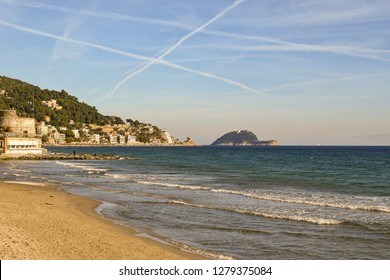 View of the sandy beach of Alassio with the Saracen Tower on the left, the Cappelletta and the Gallinara Island on the horizon, Liguria, Italy