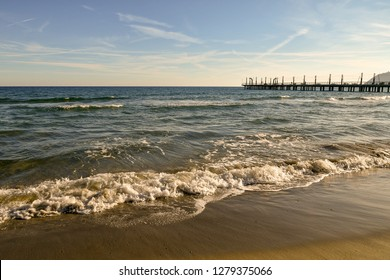 View of the sandy beach of Alassio with shore, waves and pier, Liguria, Italy