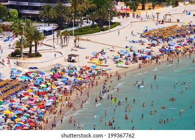View of the sandy beach full of people sunbathers and swimmers in the hot afternoon sun (Spain, Benidorm)