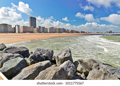 View from the sandy beach on the city. Summer day in Ostende, Belgium. A view of city buildings under construction from the desert beach