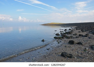 View of the sandy coast of Oosterschelde estuary on the island of Noord-Beveland, The Netherlands, with scattered black rocks on a hazy, windless day