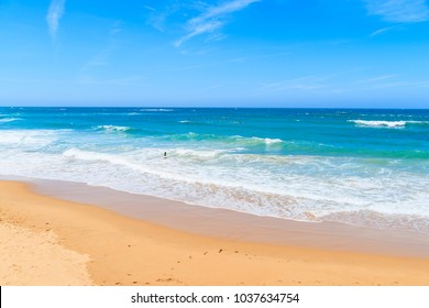 A view of sandy Praia do Amado beach and sea with waves, Portugal
