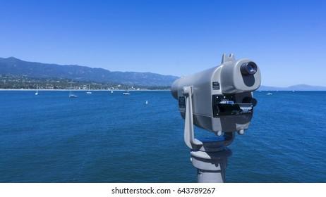 View of the Santa Barbara, California coastline in the background and a telescope.