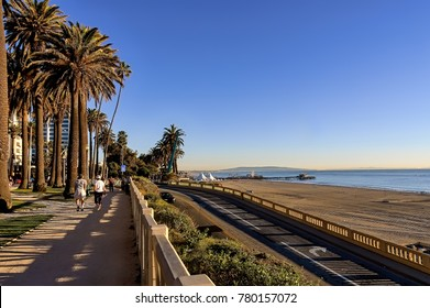 View of Santa Monica beach, California incline and Pacific Coast highway, and people walking in Palisades park.