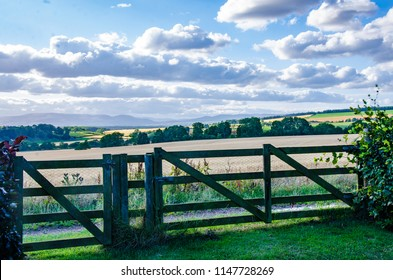 A view of a Scottish landscape looking at a wooden fence and farmland beyond.