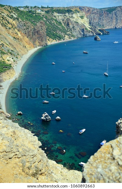 View of the sea Bay and ships from the top of the mountain on a Sunny day. View from the top. Vertical orientation.