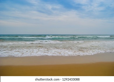 A view of sea beach of Puri with golden sand and blue sky and water