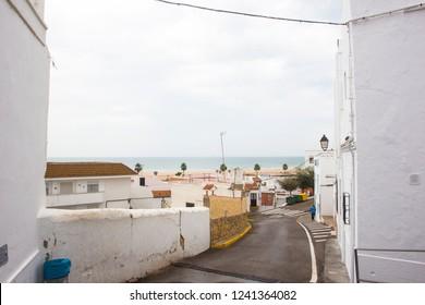 View to the sea between spanish houses in the white city of Conil de la Frontera on the Costa del luz
