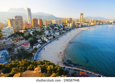 View of the sea coast with people bathing in the blue sea, on a background of city at sunset (Spain, Benidorm - Fish Eye Lens)