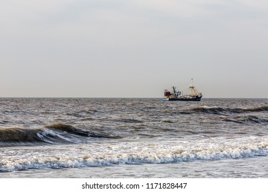view of the sea with fishing boat with a gray sky in the background in Noordwijk Holland