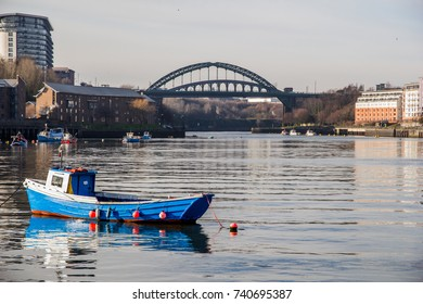 View of Sunderland's sea fishing harbour with a wooden boat reflecting in the still water and the iconic Wearmouth Bridge in the background