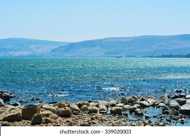 View of the Sea of Galilee from the shore, depicting some rocks, hills, and the sky.