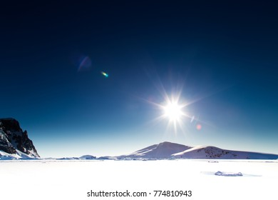 A view of the sea ice in the Antarctic during winter with the sun low on the horizon. Pleneau Bay, Antarctica