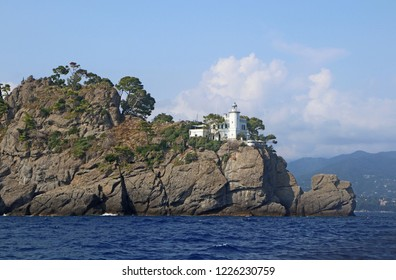 View from the sea of the Lighthouse of  Portofino on the peninsula closing the bay