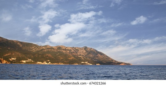 A view of the sea and mountainous coast and the blue sky with white clouds near Becici, the city of Budva, Montenegro.