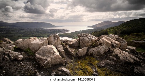 View of sea and mountains on the Irish border between North and South. Rocks and trees in foreground.