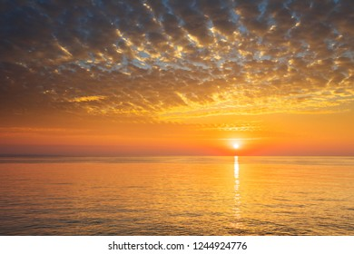 A view of the sea or ocean with a stunning sunset and feather clouds that stretch across the horizon.