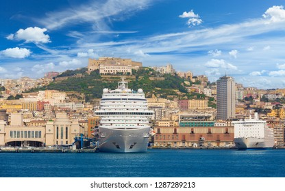 View from sea on Naples coastline, Italy. Big cruise ships are in port, cityscape in sunny weather with blue sky and white clouds.
