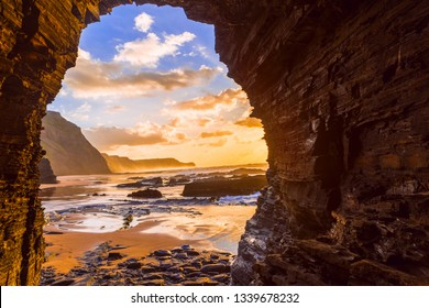 View to the sea sunset from inside a cave at Barriga Beach, Portugal.