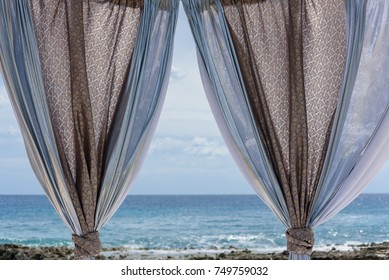 view of a sea through the curtains of a Luxury beach bed