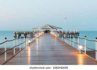 View of the sea and wooden pier with lights at sunrise, wide beach, blue sky without clouds in Belek Antalya