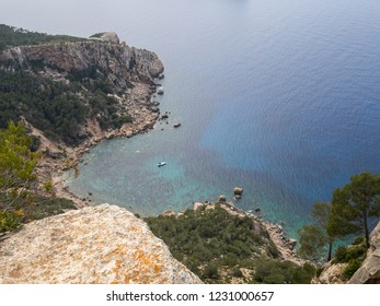 The view of seabay with white boat captured from the cliff during the GR 221 trek along the Serra de Tramuntana mountains. Mallorca, Spain.