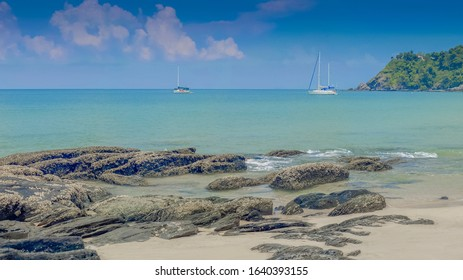 view seaside panorama of many arch rocks on white sand beach with yacth boats in blue-green sea and blue sky background, Bakantiang beach, Ko Lanta island, Krabi, southern of Thailand.