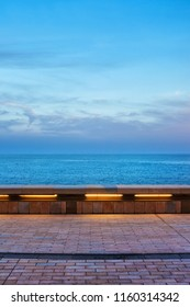 View from seaside promenade in Monaco at blue hour evening, horizon of Mediterranean Sea, composition with copy space