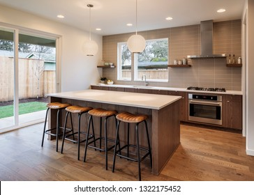 A view of the seating in the kitchen with the lights on showing the backyard