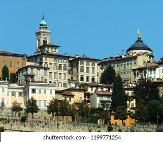 View of a section of Bergamo's historical Citta Alta (Upper Town), bright and tall against blue sky