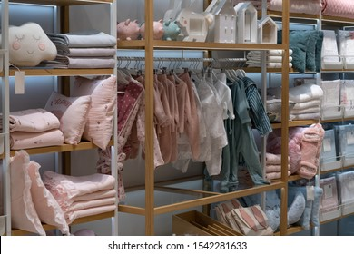 View sections of children's beautiful clothes in the store with bright lights. Shelves with goods.