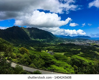 View seen from hiking on the Old Pali road of the Pali Highway, as well as Kailua and Kaneohe. Lush, varied green tropical, forest, nature and town with a bright blue sky, background of Hawaii.