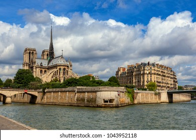 View of Seine river and famous Notre-Dame de Paris Cathedral under beautiful sky in Paris, France.