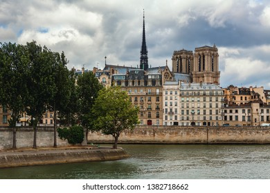 View of Seine river and spire of famous Notre-Dame de Paris cathedral among typical parisian buildings under cloudy sky.